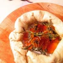 Brie envuelto en hojaldre, bañado en romero y miel, antes de entrar al horno.
